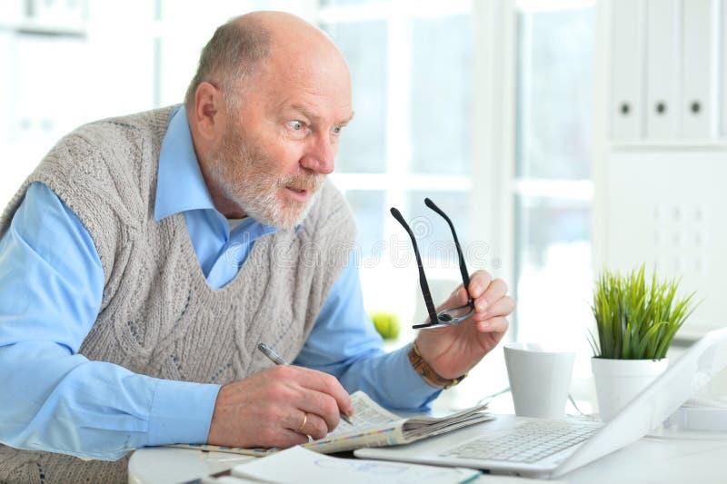 Stående av den emotionella mogna affärsmannen som i regeringsställning arbetar med bärbara datorn arkivfoto