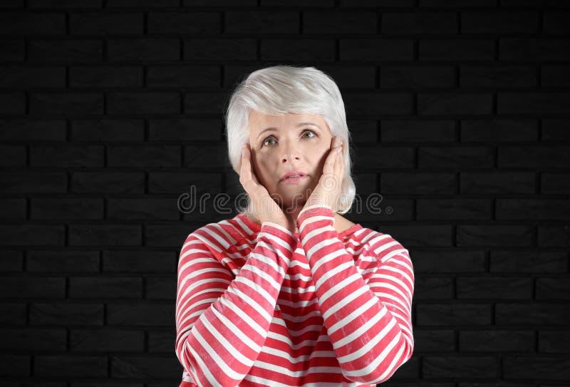 Stående av den emotionella mogna kvinnan på mörk bakgrund royaltyfri fotografi
