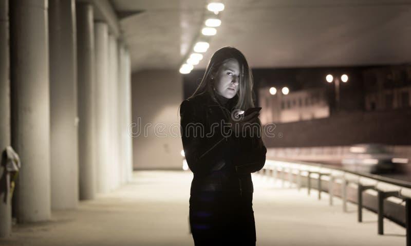 Stående av den ensamma kvinnan som använder mobiltelefonen på natten på gatan royaltyfria bilder