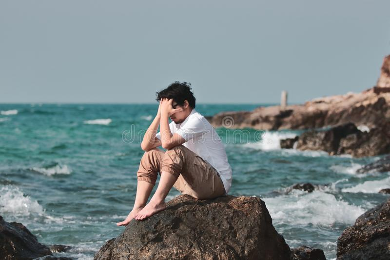 Stående av den ensamma ledsna unga asiatiska manbeläggningframsidan med händer och sammanträde på vagga av havskusten royaltyfria foton