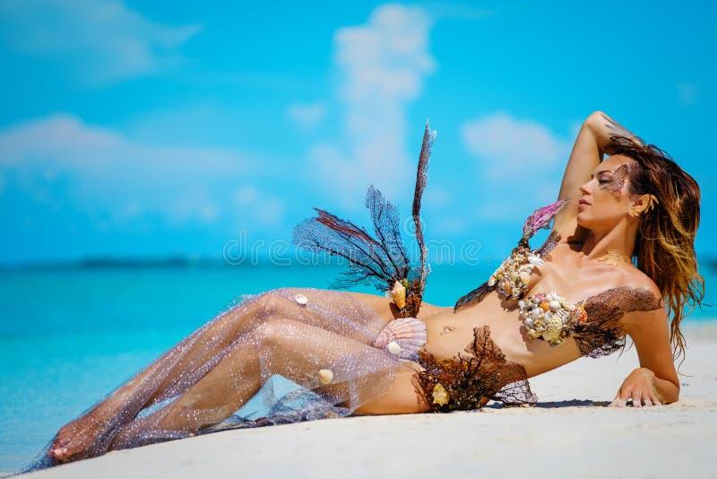 Stående av den exotiska fantasisjöjungfrun på stranden royaltyfri foto