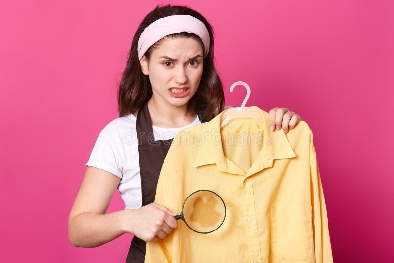 Stående av den förargade upprivna kvinnan som stnading med den gula skjortan på hängaren, innehavloupe som gör fläck större som i fotografering för bildbyråer
