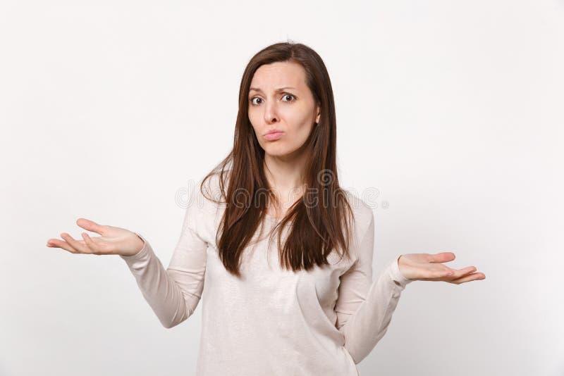 Stående av den förbryllade bekymrade missbelåtna unga kvinnan i ljus kläder som fördelar händer som isoleras på den vita väggen royaltyfria foton