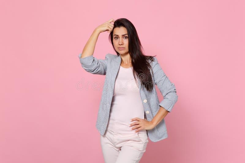 Stående av den förbryllade bekymrade unga kvinnan i det randiga omslaget som sätter handen på huvudet som isoleras på rosa pastel royaltyfri foto