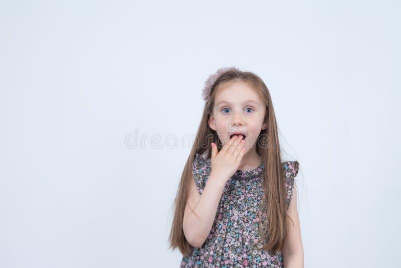 Stående av den förtjusande förvånade förvånade lilla flickan som isoleras på en vit Händer för flickabarninnehav på den förvånade royaltyfri foto