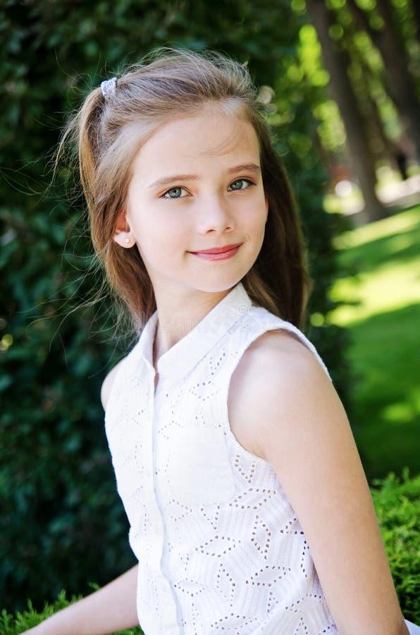 Stående av den förtjusande le liten flickabarnskolflickan utomhus royaltyfri foto