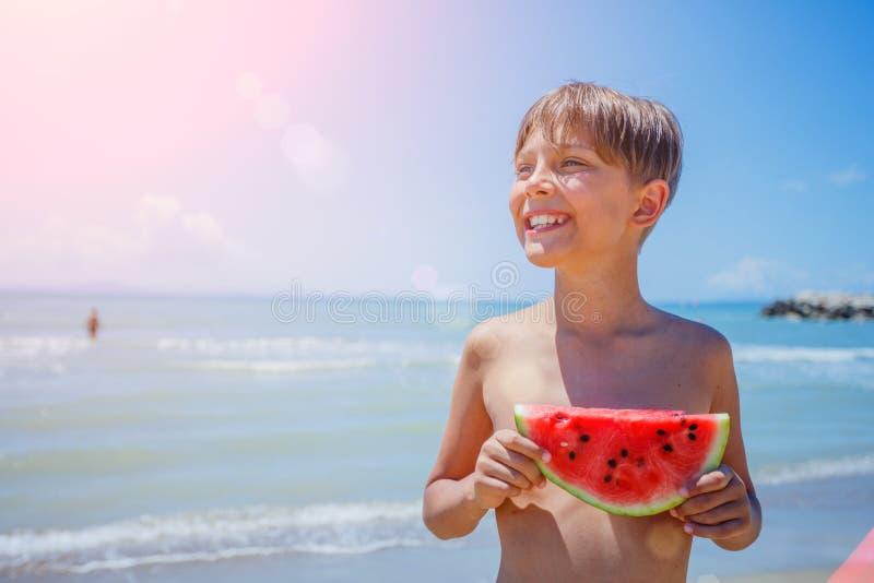 Stående av den förtjusande pojken med vattenmelon på stranden royaltyfri foto