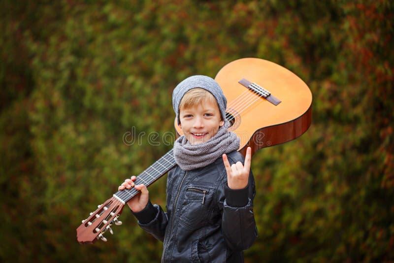 Stående av den förtjusande unga pojken med gitarren på naturbakgrund royaltyfri fotografi