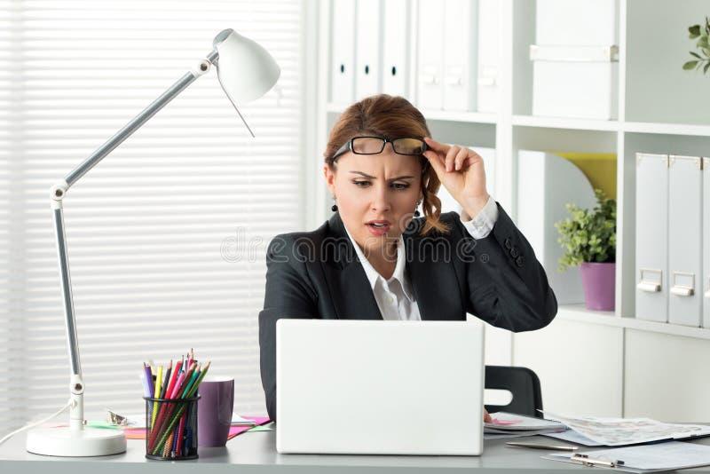 Stående av den förvånade affärskvinnan som ser bärbar datorskärmen arkivfoton