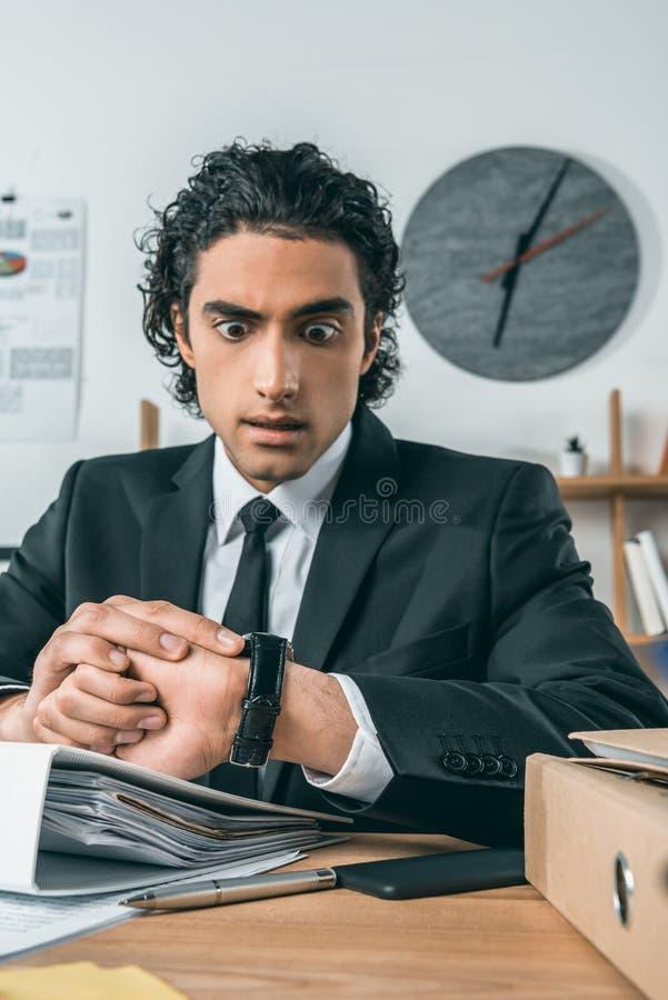 stående av den förvånade affärsmannen som kontrollerar tid på klockan, medan sitta på arbetsplatsen fotografering för bildbyråer
