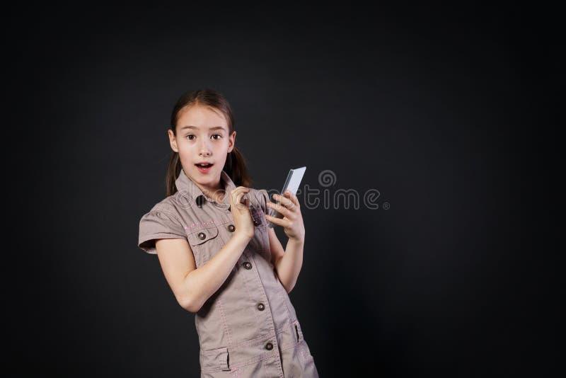 Stående av den förvånade flickapekskärmen på mobiltelefonen royaltyfri fotografi
