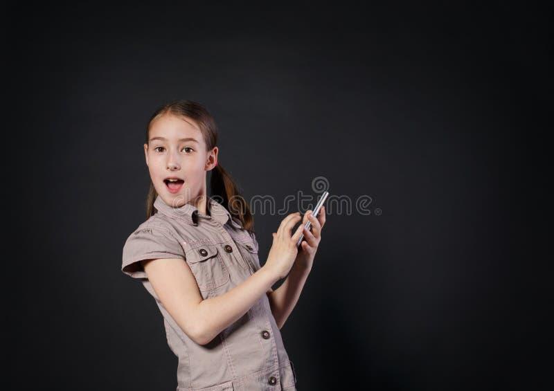 Stående av den förvånade flickapekskärmen på mobiltelefonen fotografering för bildbyråer