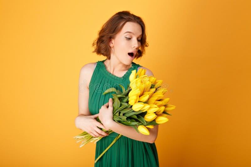 stående av den förvånade kvinnan som ser buketten av gula tulpan arkivbilder