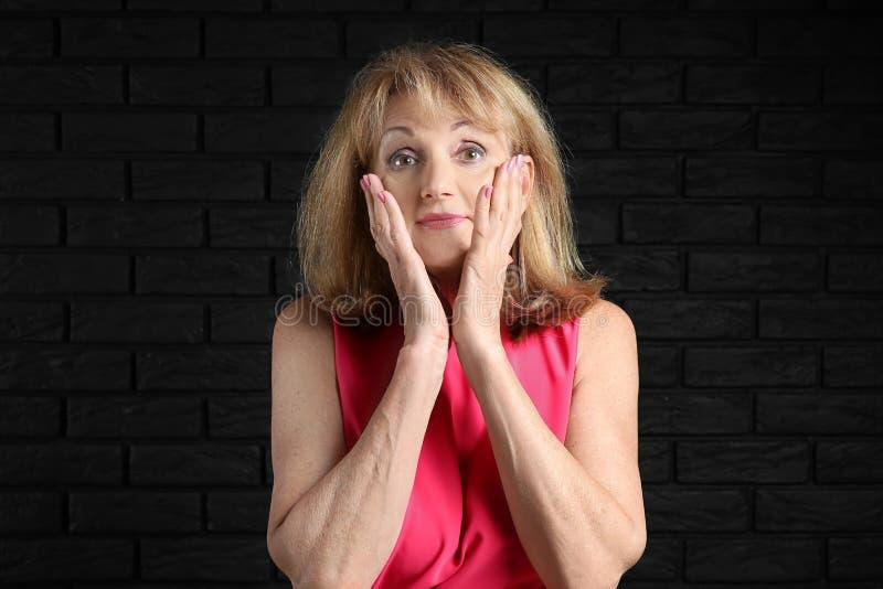 Stående av den förvånade mogna kvinnan på mörk bakgrund fotografering för bildbyråer