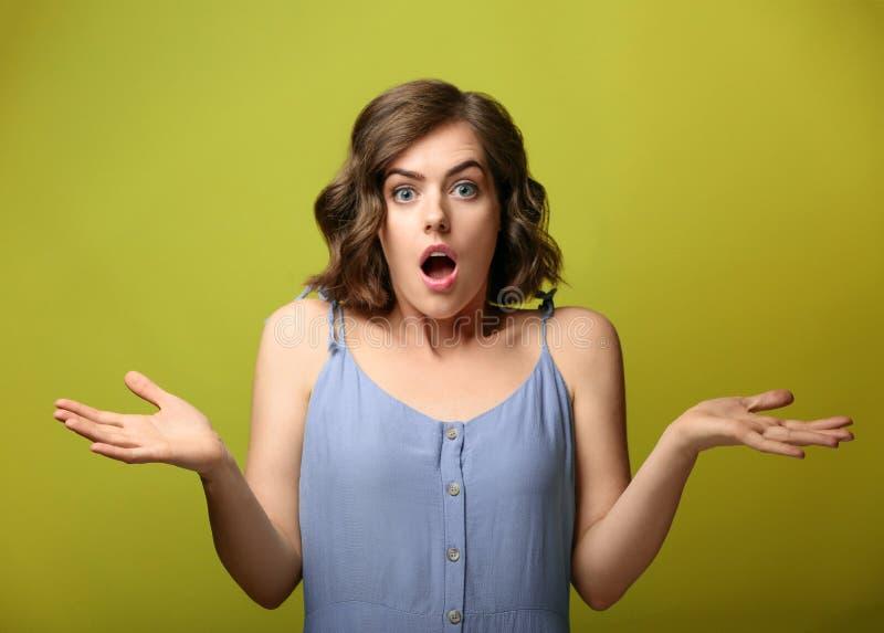 Stående av den förvånade unga kvinnan på färgbakgrund fotografering för bildbyråer
