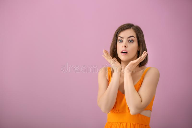 Stående av den förvånade unga kvinnan på färgbakgrund arkivfoto