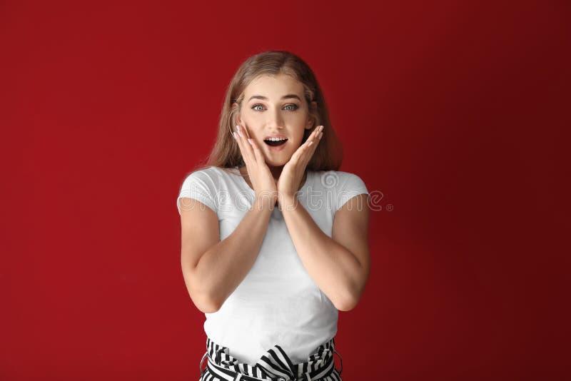 Stående av den förvånade unga kvinnan på färgbakgrund royaltyfria bilder