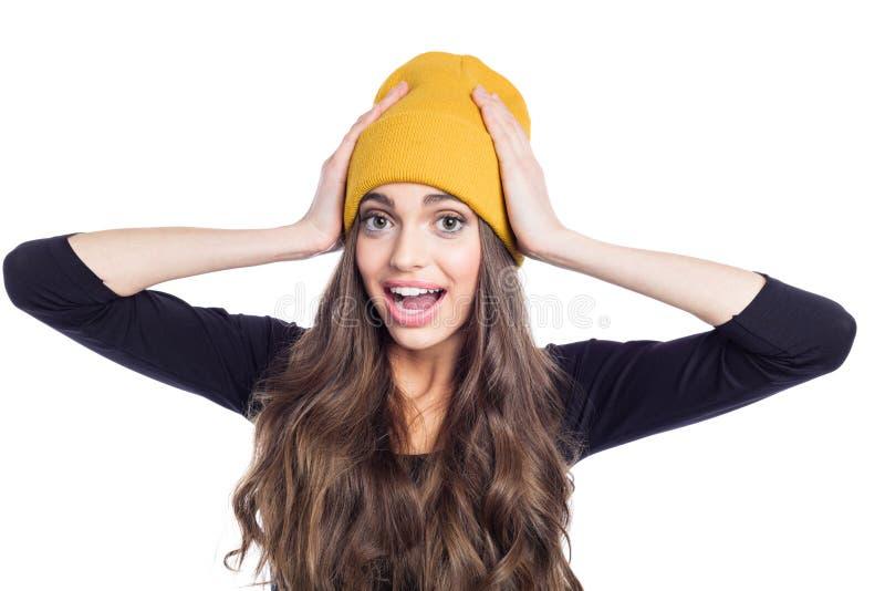 Stående av den förvånade unga kvinnan som bär den gula beaniehatten arkivbild