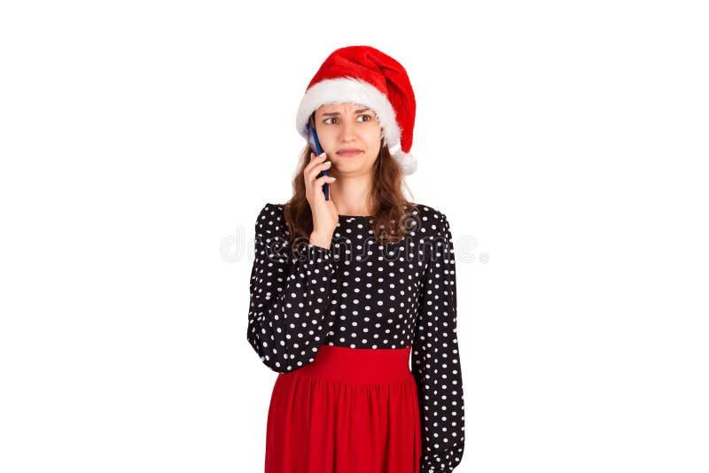 Stående av den förvirrade unga damen i klänning som talar på hennes telefon emotionell flicka i den Santa Claus julhatten som iso arkivbilder