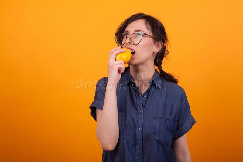 Stående av den förvirrade unga kvinnan för beaufitul, medan bitting en ny apelsin över gul bakgrund royaltyfria foton