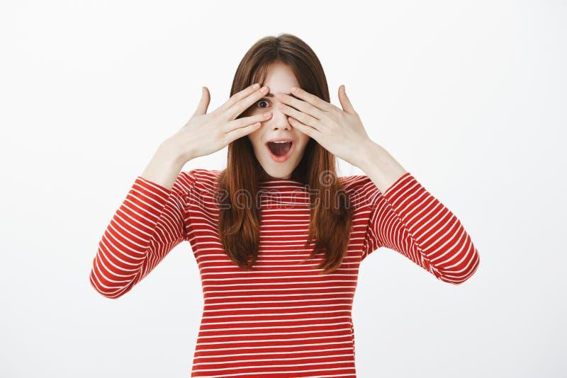 Stående av den fantastiska europeiska flickan i tillfällig kläder som täcker ögon och kikar till och med fingrar som är förvånade royaltyfria foton