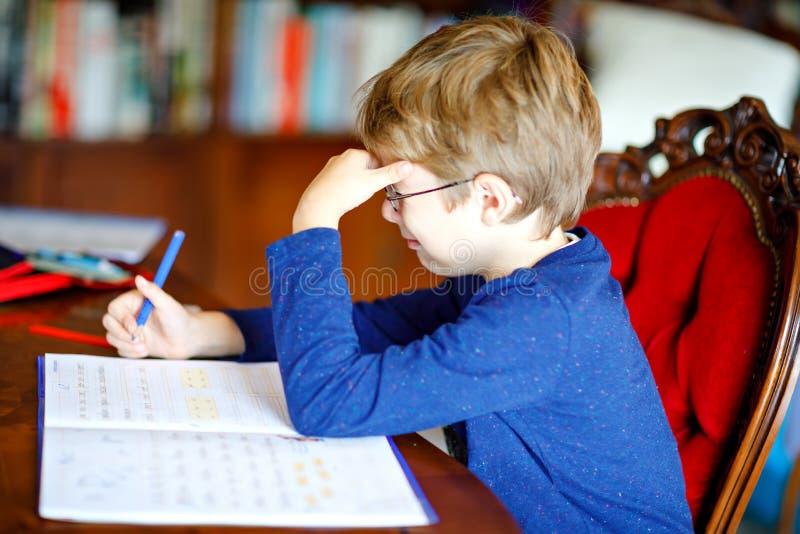 Stående av den frustrerade skriande ledsna skolaungepojken hemma som gör läxa Handstil för litet barn med färgrika blyertspennor royaltyfri bild
