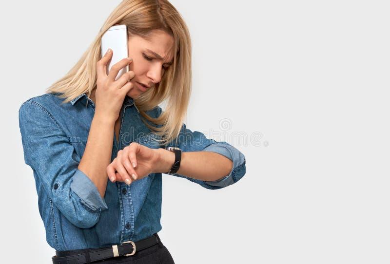 Stående av den frustrerade unga blonda kvinnan som talar på mobiltelefonen som ser klockan, därför att hennes kollega är sen royaltyfri foto
