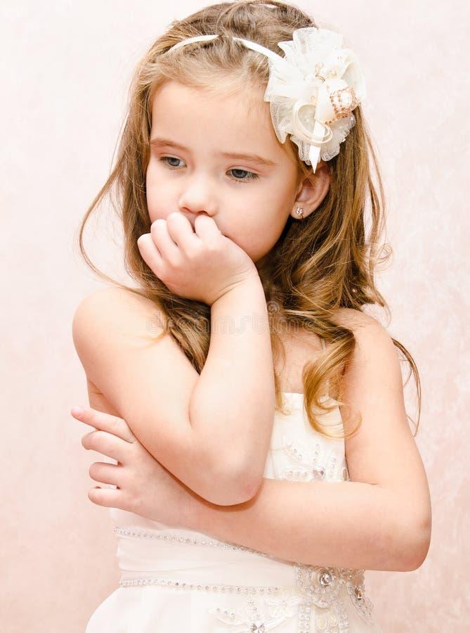 Stående av den fundersamma förtjusande lilla flickan i prinsessaklänning arkivbild