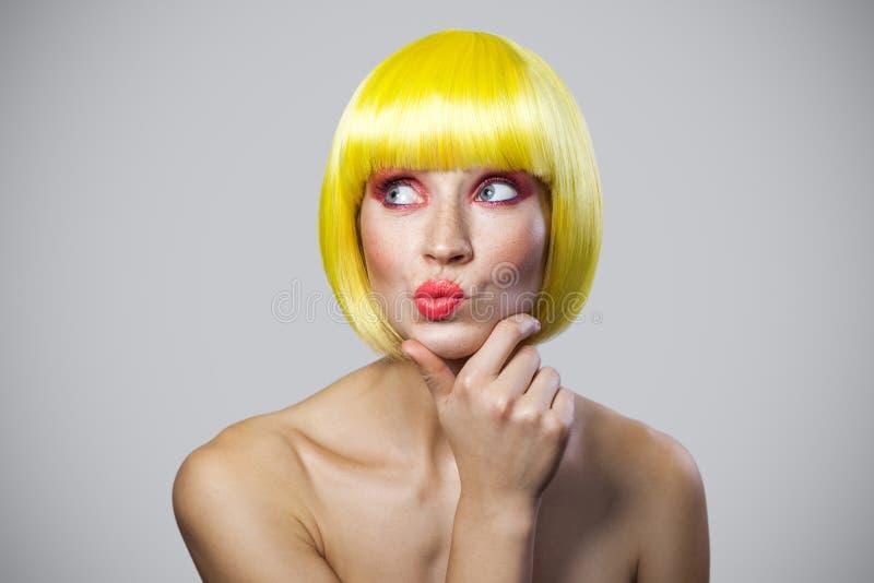 Stående av den fundersamma gulliga unga kvinnan med fräknar, röd makeup och gul peruk som thouching hennes haka, se bort och tänk fotografering för bildbyråer