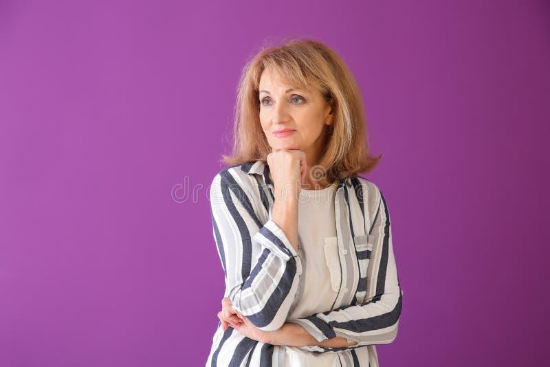 Stående av den fundersamma mogna kvinnan på färgbakgrund royaltyfri bild