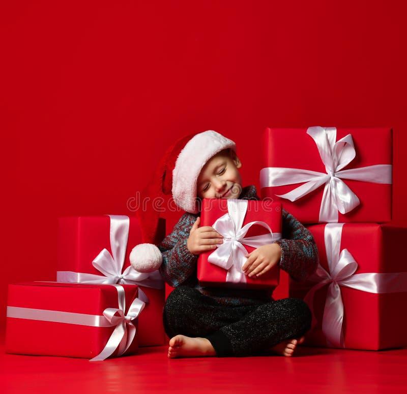Stående av den fundersamma pojken i jultomtenhatten som isoleras på röd bakgrund arkivbilder