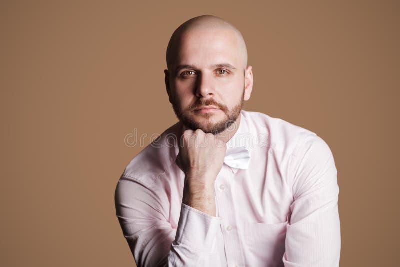 Stående av den fundersamma stiliga skäggiga skalliga mannen i ljus - rosa färg s royaltyfri foto