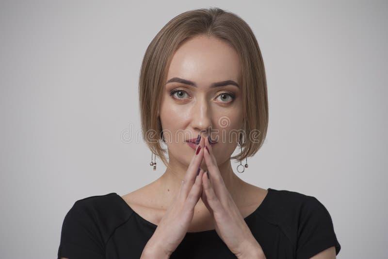Stående av den fundersamma unga kvinnan som pekar hennes fingrar till kanter royaltyfria bilder