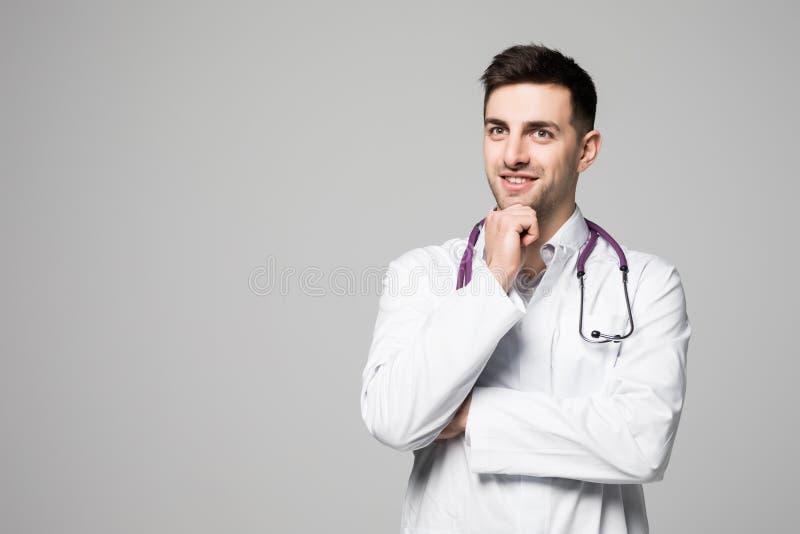 Stående av den fundersamma unga manliga doktorn med anseende för iklädd likformig för stetoskop med armen på hakan och att se bor arkivbilder