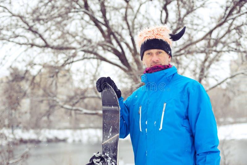 Stående av den galna mannen i en rolig hatt med snowboarden royaltyfri fotografi