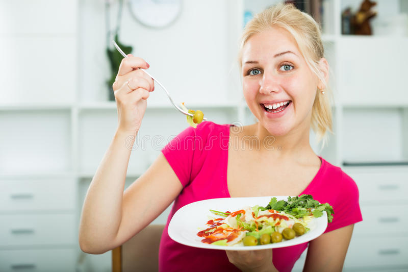 Stående av den glade blonda flickan som äter sallad fotografering för bildbyråer
