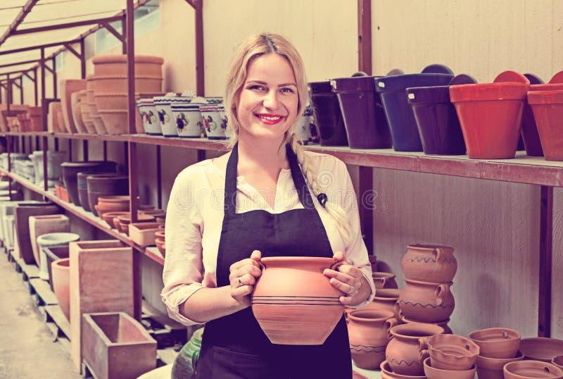 Stående av den glade kvinnakrukmakeriarbetaren med keramisk lerkärl royaltyfri foto