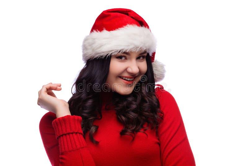 Stående av den glade kvinnan som bär den santa hatten i röd tröja och att le i huvudsak att vara skämtsamt och känslobetonat, iso arkivbild