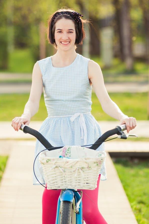 Stående av den glade kvinnlign som rider en cykel i parkera arkivfoto