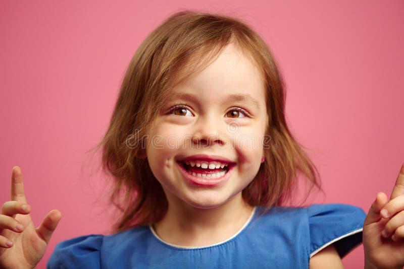 Stående av den glade lilla flickan i bra lynne på isolerad rosa bakgrund royaltyfria bilder
