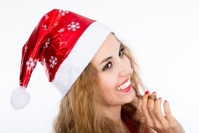 Stående av den glade nätta kvinnan i rött skratta för Santa Claus hatt arkivbild