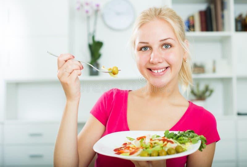 Stående av den glade unga blonda flickan som äter sallad fotografering för bildbyråer