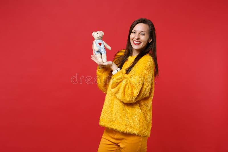 Stående av den glade unga kvinnan i den gula leksaken för björn för nalle för pälströjainnehav som flotta isoleras på ljus röd vä arkivfoto