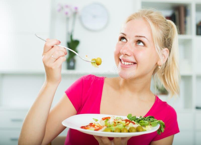 Stående av den glade vuxna blonda flickan som äter sallad royaltyfri fotografi