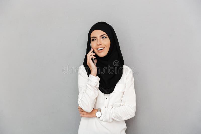 Stående av den gladlynta arabiska kvinnan i religiös sjalettspeakin arkivfoton