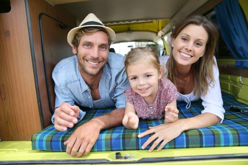 Stående av den gladlynta familjen i den campa skåpbilen arkivbild