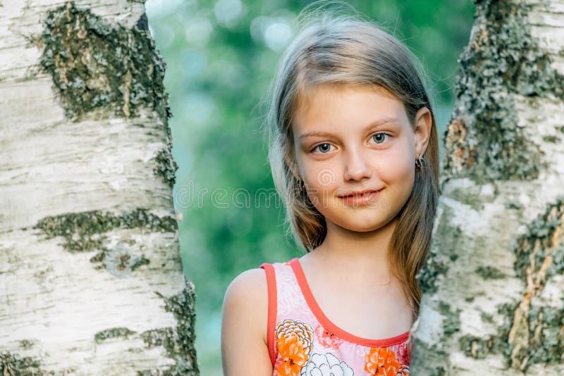 Stående av den gladlynta gulliga lilla flickan nära björken arkivfoto