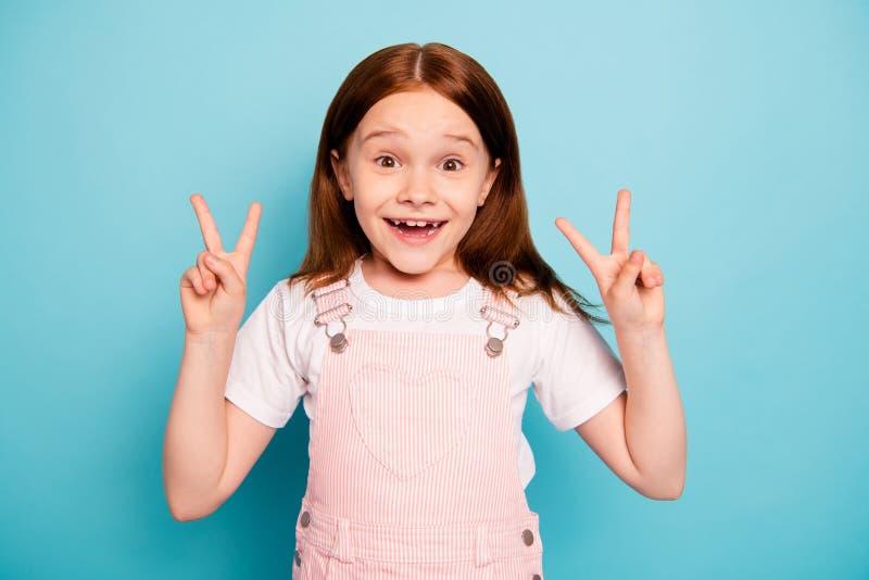 Stående av den gladlynta gulliga ungen att göra isolerad blå bakgrund för v-tecken två skratt skratt royaltyfria foton