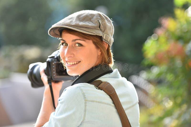 Stående av den gladlynta kvinnafotografen på arbete royaltyfri foto