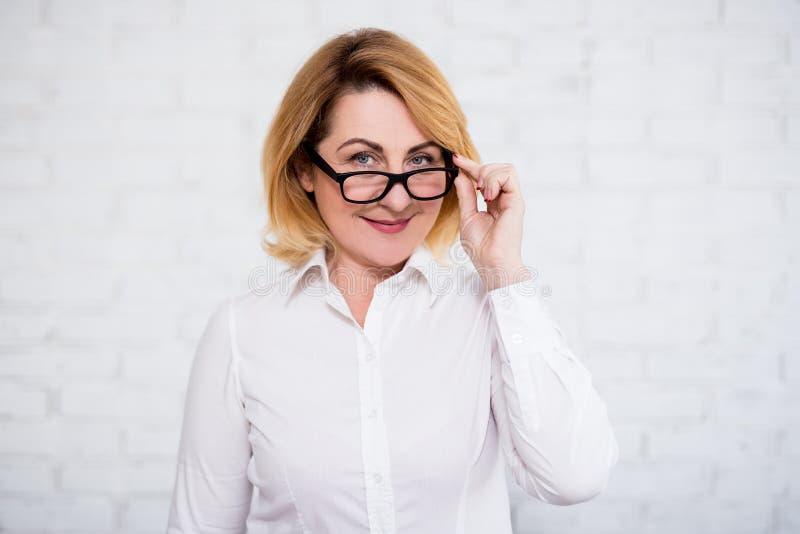 Stående av den gladlynta kvinnan för mogen affär i glasögon som poserar över den vita väggen arkivfoton